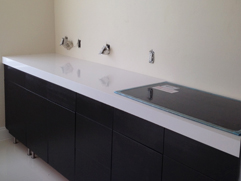 Compac Quartz Absolute Blanc Countertop featuring Black Cabinets and Glass Cook Top