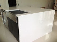 Absolute Blanc waterfall Island Countertop with Stainless steel farmer sink and Black Cabinets